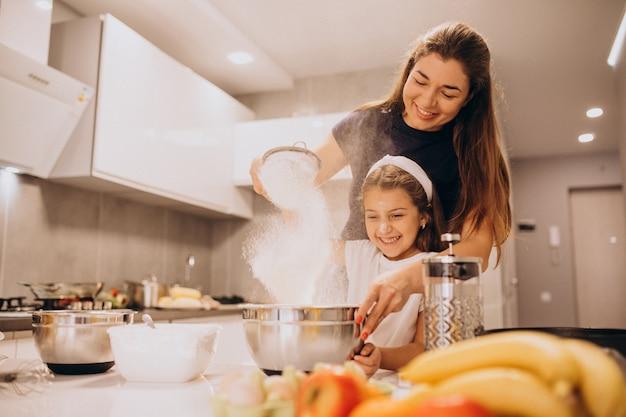 一緒にキッチンで焼く娘を持つ母 無料写真
