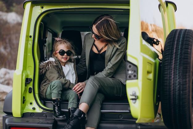 車の後ろに座っている彼女の小さな娘を持つ母 無料写真