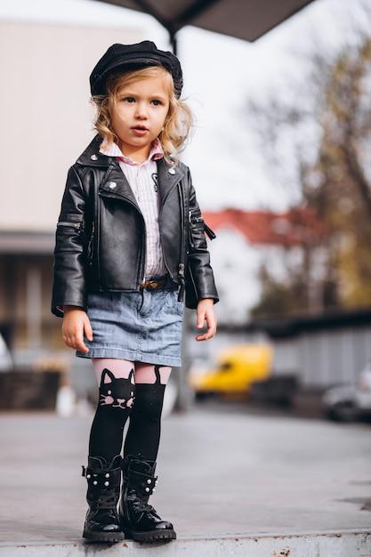 Маленькая девочка, одетая в модный наряд в парке Бесплатные Фотографии