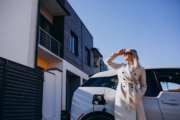 Женщина заряжает электро автомобиль возле своего дома Бесплатные Фотографии