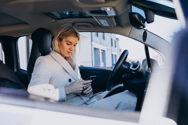 Женщина сидит внутри электро автомобиля во время зарядки Бесплатные Фотографии