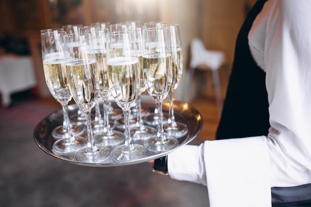 レストランのトレイで飲み物を提供するウェイター 無料写真