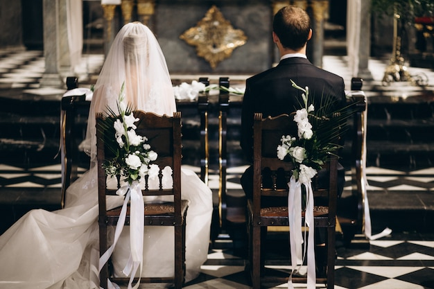 結婚式の日に椅子に座っている新郎新婦、後ろから 無料写真