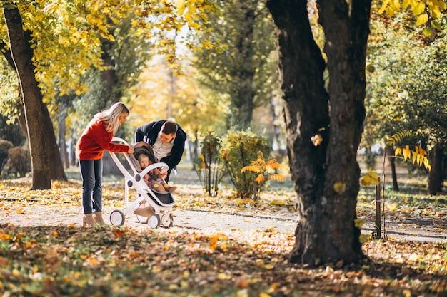 Семья с дочерью в детской коляске гуляет по осеннему парку Бесплатные Фотографии