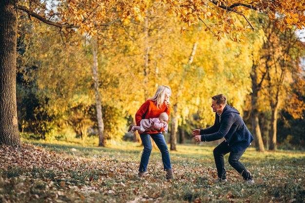 Семья с маленькой дочкой гуляет в осеннем парке Бесплатные Фотографии