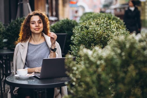 カフェの外のコンピューターで作業して若い実業家 無料写真