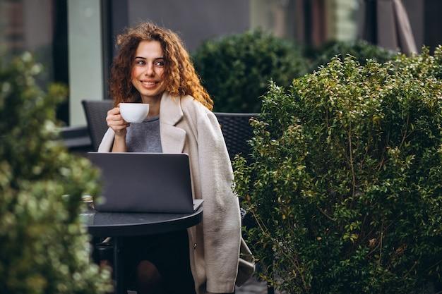 Молодая коммерсантка работая на компьютере вне кафе Бесплатные Фотографии