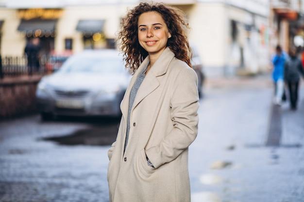 通りの外の巻き毛を持つ若い女性 無料写真
