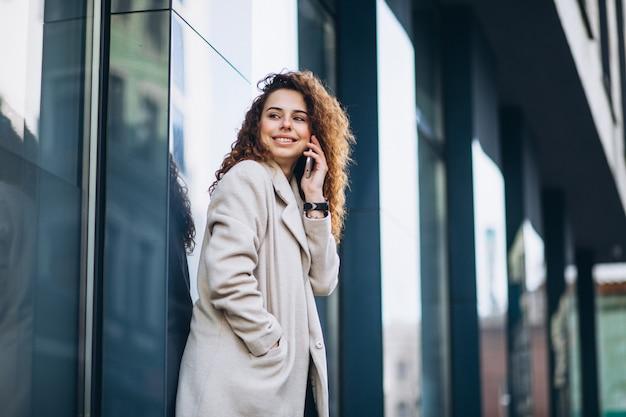 通りで電話を使用して巻き毛を持つ若い女性 無料写真