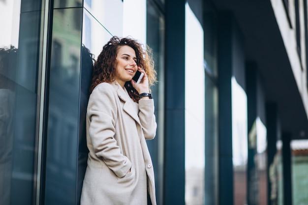Молодая женщина с вьющимися волосами, с помощью телефона на улице Бесплатные Фотографии