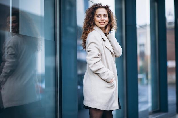 Молодая женщина с вьющимися волосами за пределами улицы Бесплатные Фотографии