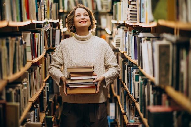 Молодая женщина учится в библиотеке Бесплатные Фотографии