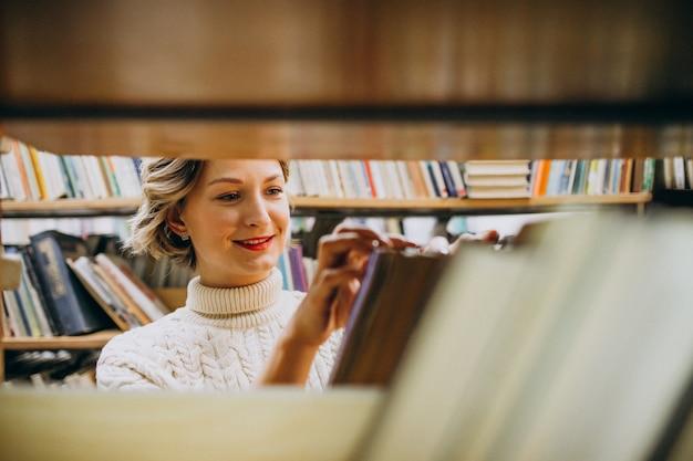 Молодая женщина, выбирая книгу в библиотеке Бесплатные Фотографии