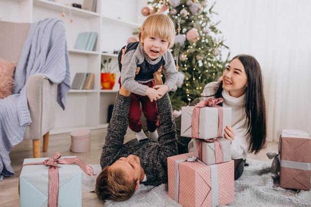クリスマスツリーで幼い息子と若い家族 無料写真