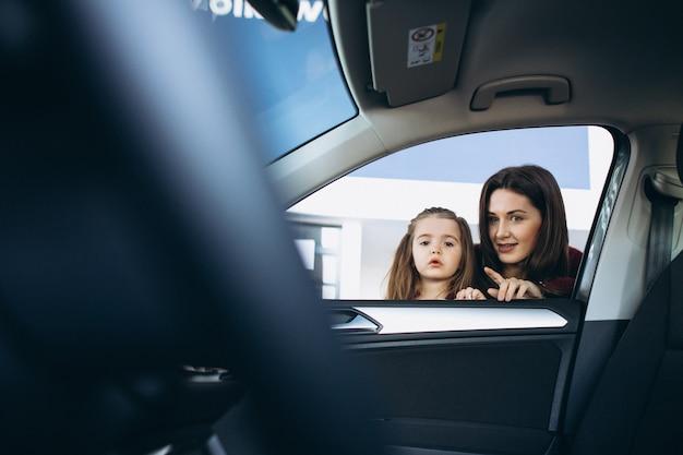 車のショールームで車の中を探している娘を持つ母 無料写真