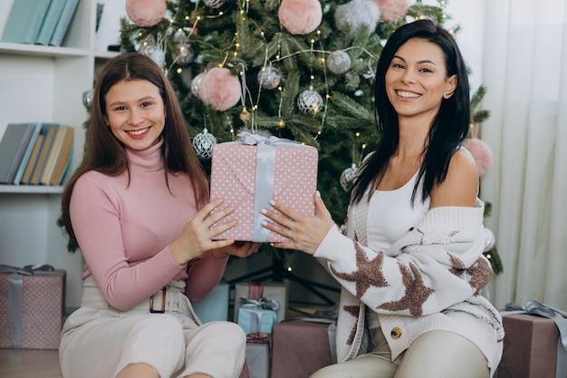 クリスマスと大人の娘を持つ母がクリスマスツリーでプレゼントします。 無料写真