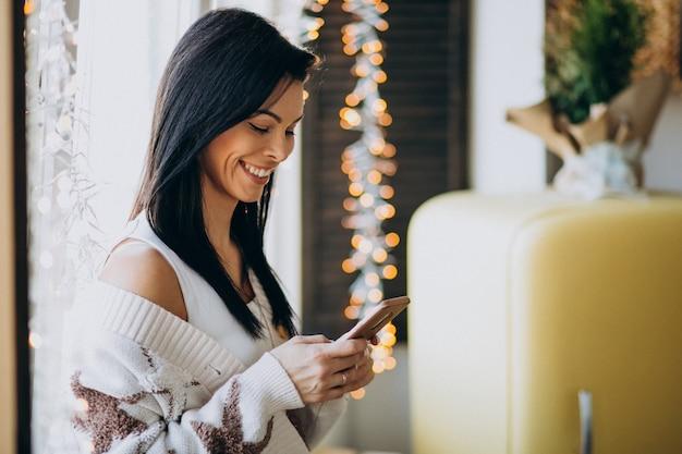 Молодая женщина с помощью телефона и стоя у окна Бесплатные Фотографии