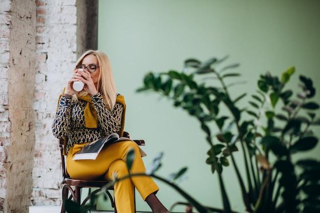 コーヒーを飲みながら雑誌を読んで椅子に座っている大人の女性 無料写真
