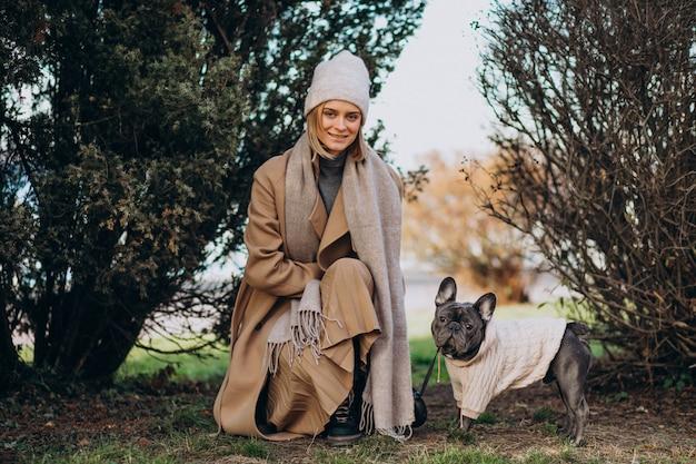 Красивая женщина с французским бульдогом гуляя в парк Бесплатные Фотографии