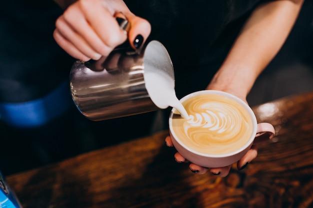 コーヒーショップでコーヒーにミルクを注ぐバリスタ 無料写真