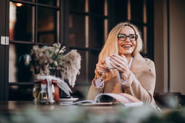 カフェの外に座って、雑誌を読んでコートで高齢者の実業家 無料写真