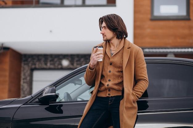 冬時間に屋外でコーヒーを飲む若いハンサムな男 無料写真