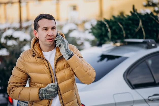 上のクリスマスツリーと車で電話で話しているハンサムな男 無料写真