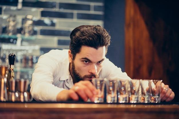 Красивый бармен человек делает пить и коктейли за прилавком Бесплатные Фотографии