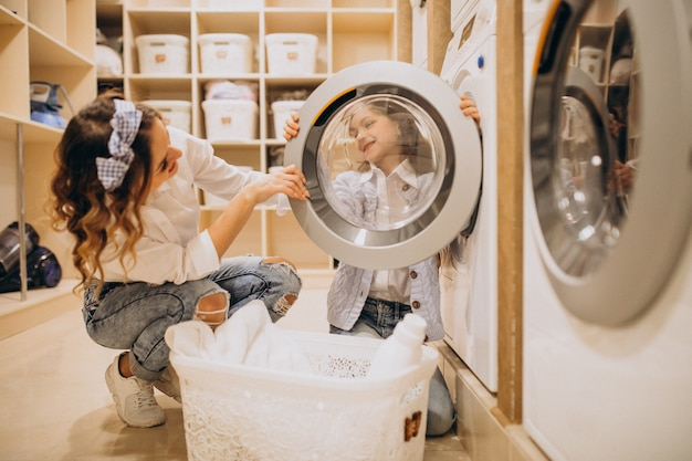 Мать с дочерью стирает в прачечной самообслуживания Бесплатные Фотографии