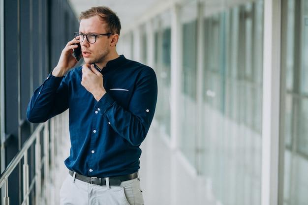 オフィスで電話で話している若いハンサムな男 無料写真