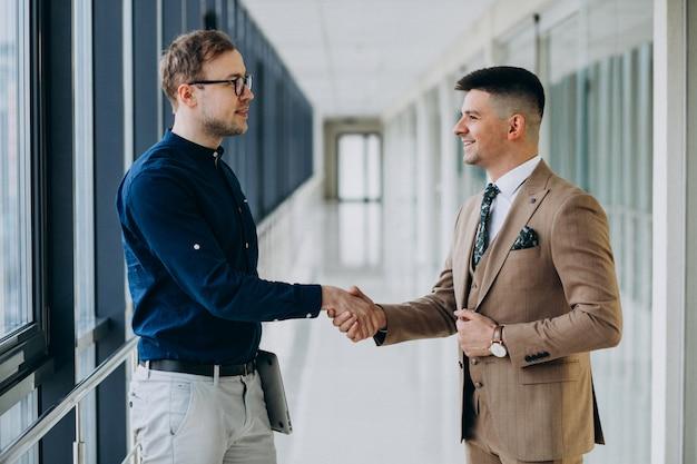 Двое мужчин-коллег в офисе, стоя с ноутбуком Бесплатные Фотографии