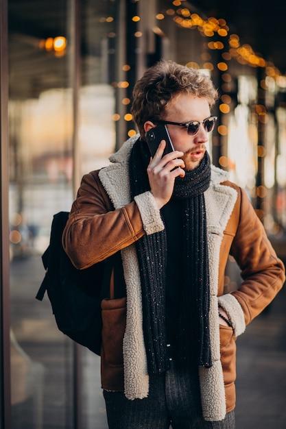 空港で電話で話している若いハンサムな男 無料写真