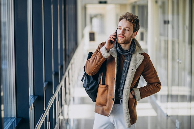 電話で話している空港で若いハンサムな男 無料写真