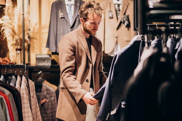 Молодой красавец, выбирая одежду в магазине Бесплатные Фотографии