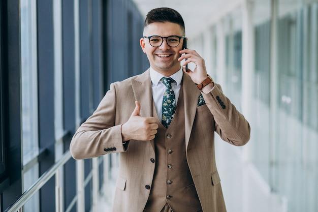 オフィスで電話で立っている若いハンサムなビジネス人 無料写真