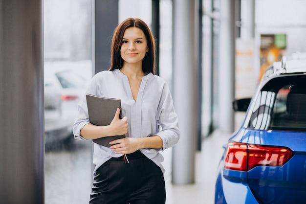 車を選択する車のショールームで若い女性 無料写真