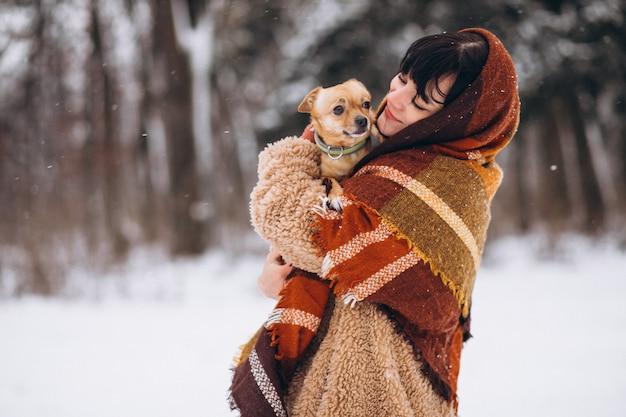 Молодая женщина вне парка с ее маленькой собакой зимой Бесплатные Фотографии