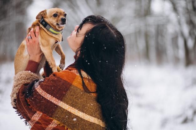冬に彼女の小さな犬と公園の外の若い女性 無料写真