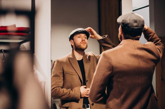 お店で帽子を選択する若いハンサムな男 無料写真