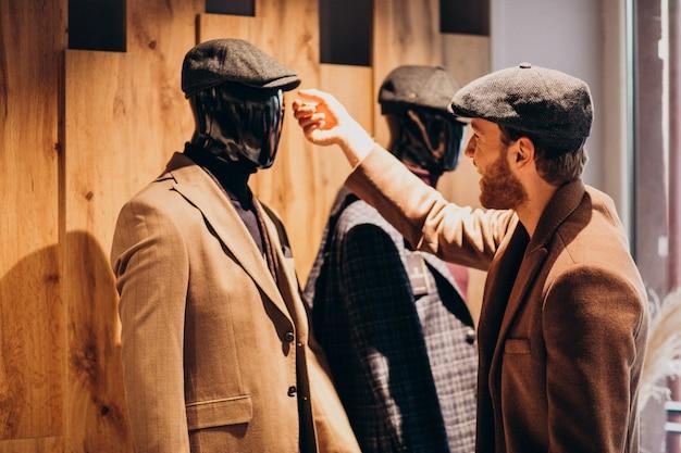 Молодой красавец, выбирая шляпу в магазине Бесплатные Фотографии