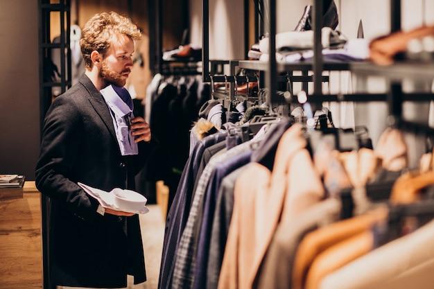 Молодой красавец, выбирая рубашку в магазине Бесплатные Фотографии