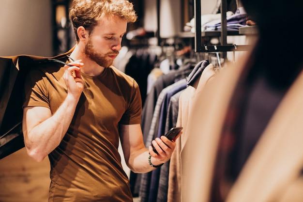Молодой человек в магазине мужской одежды разговаривает по телефону Бесплатные Фотографии