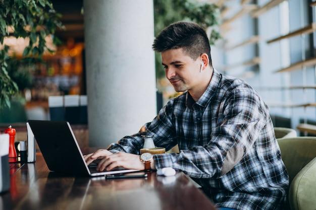 Молодой красивый деловой человек, используя ноутбук в кафе Бесплатные Фотографии