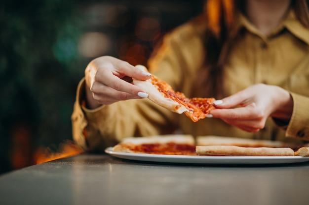 バーでピザを食べる若いきれいな女性 無料写真