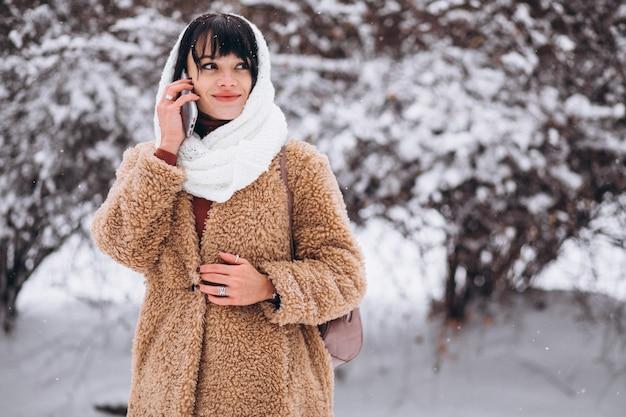 Молодая счастливая женщина в теплой одежде в зимнем парке Бесплатные Фотографии