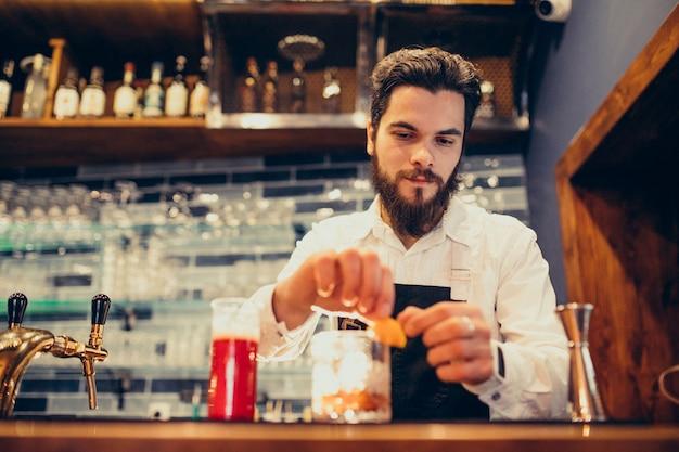 Красивый бармен делает пить и коктейли на прилавке Бесплатные Фотографии