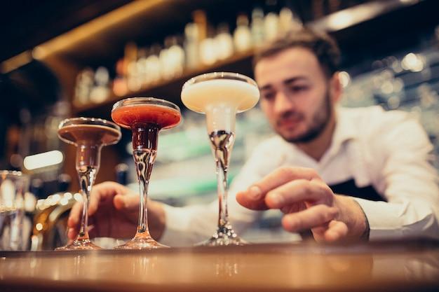 カウンターで飲むとカクテルを作るハンサムなバーテンダー 無料写真