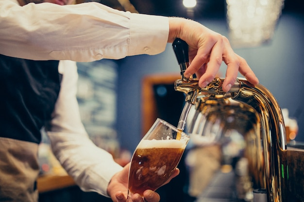 パブでビールを注ぐ男性バーテンダー 無料写真