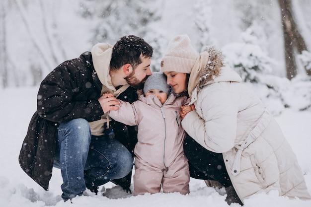 雪だらけの冬の森の小さな娘と若い家族 無料写真