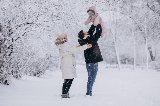 Молодая семья с маленькой дочерью в зимнем лесу, полном снега Бесплатные Фотографии